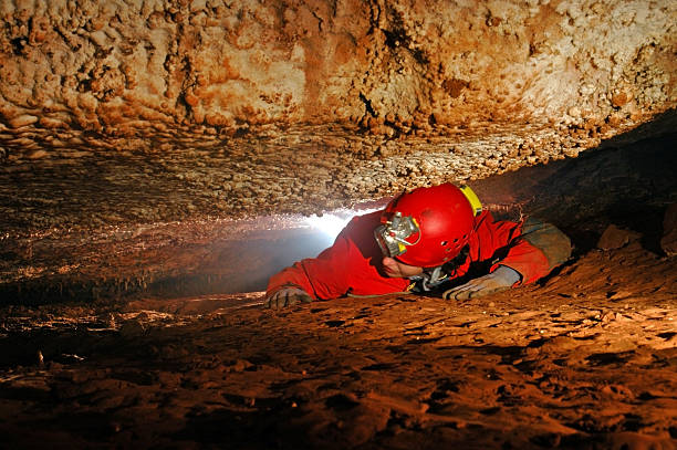 Narrow cave passage with a cave explorer Narrow cave passage with a spelunker explorer narrow stock pictures, royalty-free photos & images