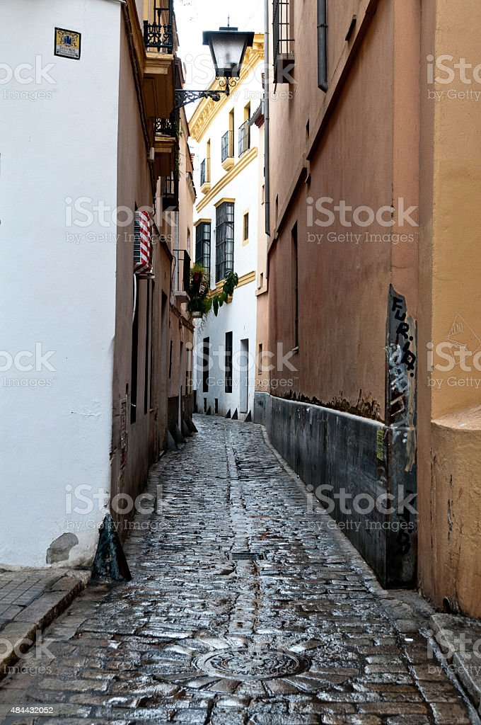 Narrow cobblestone street in the Santa Cruz district of Seville stock photo