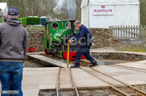 Shelley, UK: April 8, 2018: A man watches from a platform whilst a narrow gauge steam train is turned round on a manually operated turntable.