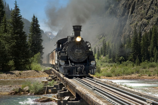 Narrow gauge steam powered train crosses the Animus River on its way to Silverton from Durango, Colorado.