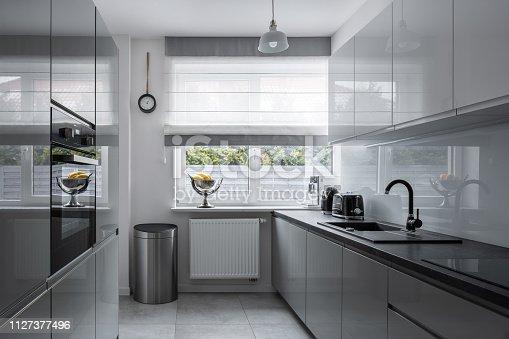 istock Narrow kitchen with modern furniture 1127377496