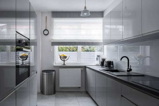 Narrow kitchen with modern furniture Narrow kitchen with window and modern, gray furniture narrow stock pictures, royalty-free photos & images