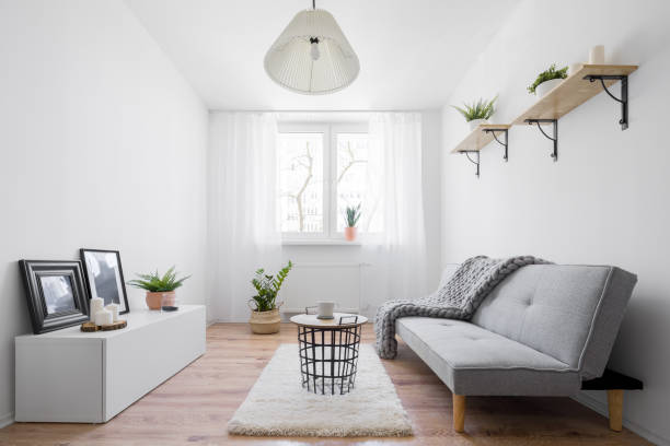 Narrow living room Narrow and stylish living room with furniture in scandinavian style narrow stock pictures, royalty-free photos & images