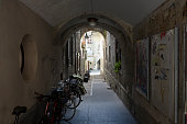 Bern, Switzerland - April 20, 2017: Narrow passage leads though the gate under the building from one street to another. Several parked bikes can be seen in the shaded gate. This is one of the countless wonderful places in Switzerland, which is a tourist attraction often visited by many tourists from all over the world.