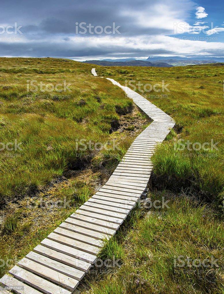 Narrow path up a hill toward the cloudy sky stock photo