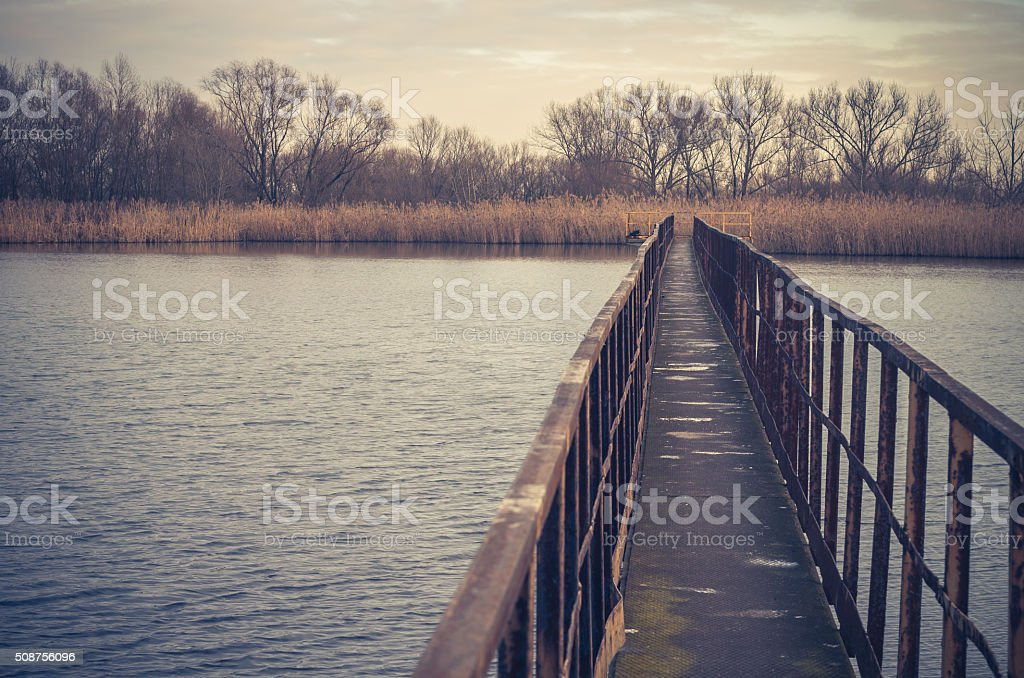 Narrow steel bridge over autumn lake stock photo