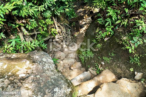 istock Narrow stone staircase slope down way at the hill background. Narrow rock steps down alley with rock wall and tree 1284697611