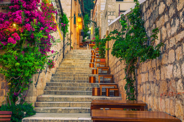 Narrow street and street cafe decorated with flowers, Hvar, Croatia stock photo