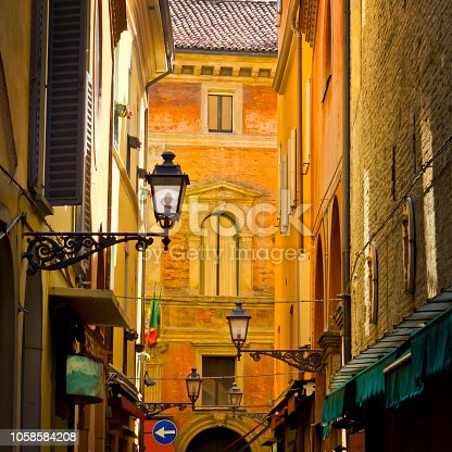Square picture of a narrow street in Bologna with street lanterns and orange walls