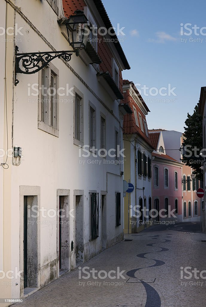 Narrow street in Cascais with typical cobblestone wave pattern royalty-free stock photo