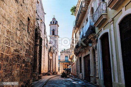 Narrow cobblestone street leading to the Cathedral Square in Old Havana in Cuba, with one of the towers of the baroque Cathedral to be seen.