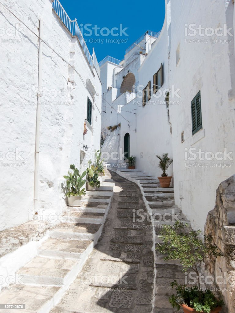 Narrow street in the white city of Ostuni, Puglia, Italy stock photo