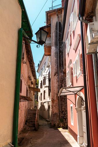 Narrow street of ancient Lovran town on Adriatic coast, Croatia.