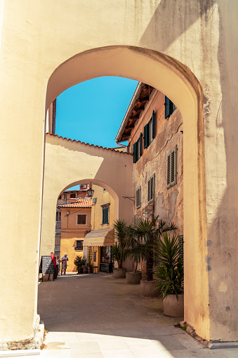 Lovran Croatia - 05 June 2021: Narrow street of ancient old town with arc, vintage buildings and palm trees. Lovran.