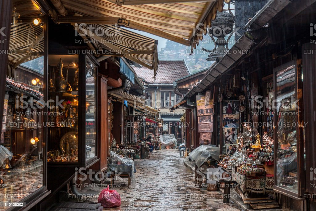 Narrow street of the Bascarsija district of Sarajevo, with typical metal copper crafts being produced with ottoman techniques. Bascarsija is the symbol of Sarajevo, with its oriental architecture stock photo