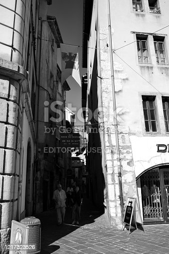 Chambéry, France - August 11th 2017 : Narrow street with pedestrians and shops.