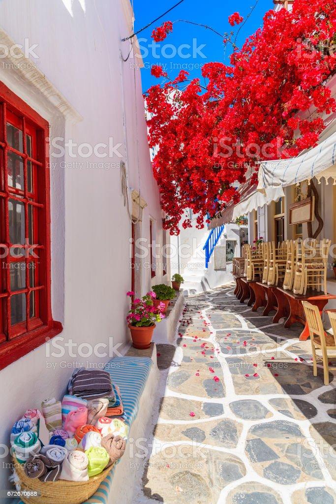 Uma rua estreita com flor decorado casas na cidade de Mykonos, ilhas Cíclades, Grécia - foto de acervo