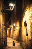 Street lanterns illuminating an ancient narrow street in the old city of Barcelona, Spain.