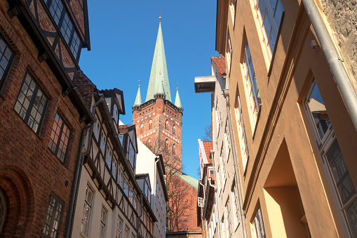 narrow urban street and Church in the old town Luebeck