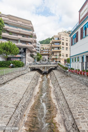 istock Narrow water stream flowing down through stone paved riverbed built to protect from flash flooding in Montreux town,  Vaud, Switzerland 1165314599