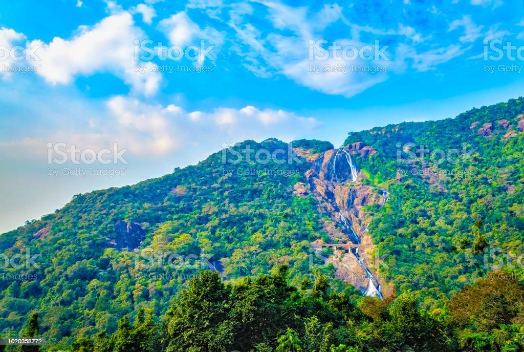 Chute d'eau étroit traverse une montagne verte - Photo
