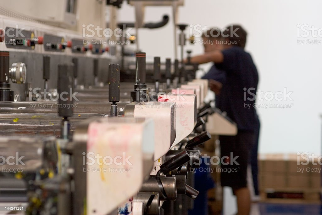 A narrow web flexo label press being prepared for printing by two...