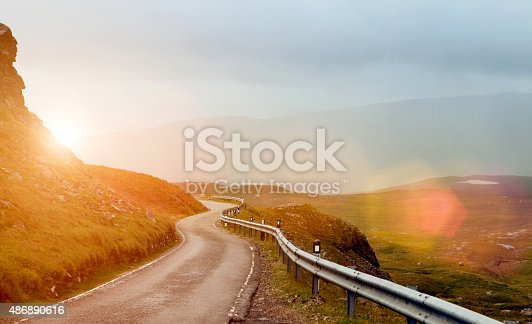 istock Narrow winding road in a valley at sunset 486890616