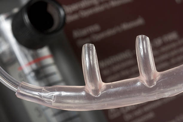 Nasal Cannula Oxygen Tube Shown here is a close up of a nasal cannula used to deliver oxygen to a medical patient.  Behind in soft focus is an oxygen concentrator with a flowmeter. oxygen tube stock pictures, royalty-free photos & images