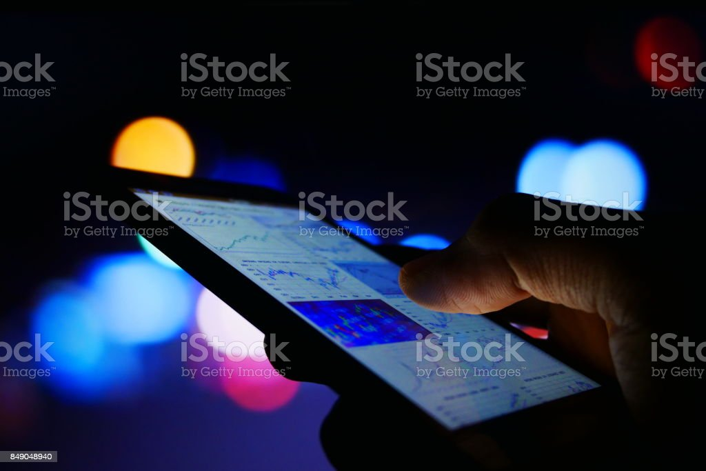 nasdaqusing phone for business close up low light stock photo