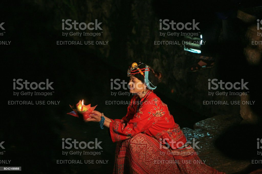 Nashi woman with a candle offering in Lijiang, Yunnan, China stock photo