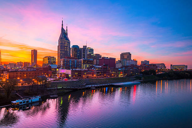Nashville at Dusk with Beautiful Sky and Water Downtown Nashville skyline with a beautiful pink, orange, and blue sunset, with the blue and pink of the sky reflected on the Cumberland River. tennessee stock pictures, royalty-free photos & images