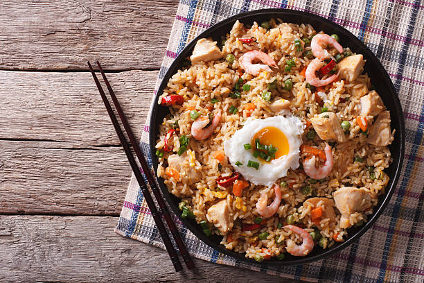 nasi goreng with chicken, prawns, egg and vegetables horizontal Asian fried rice nasi goreng with chicken, prawns, egg and vegetables horizontal view from above fried rice stock pictures, royalty-free photos & images