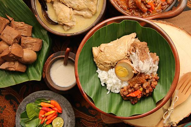 Nasi Gudeg Jogja Surrounded with the Individual Dishes Nasi Gudeg or Rice Dish with Gudeg is Jogjakarta's signature dish. It is steamed rice with Gudeg (jack fruit stew drizzled with thick coconut cream) with Opor Ayam (chicken with white curry) and Sambal Goreng Krecek (spicy stew of cattle skin crackers and red bean). The Nasi Gudeg is plated on an earthenware plate that lined with banana leaf. A pair of wooden spoon and fork is placed next to the plate. The plate and cutleries are set on a wooden block. Surrounding the plate are the dishes that make up the complete meal. Added for decorative purpose, an arrangement of red chili, lime halves and lime leaves in a traditional stoneware mortar. indonesian ethnicity stock pictures, royalty-free photos & images