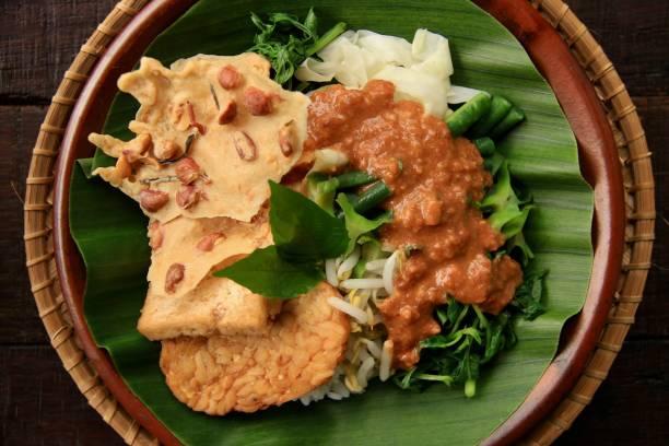 nasi pecel, einem traditionellen javanischen essen reis mit gemüsesalat - erdnusssalatdressings stock-fotos und bilder