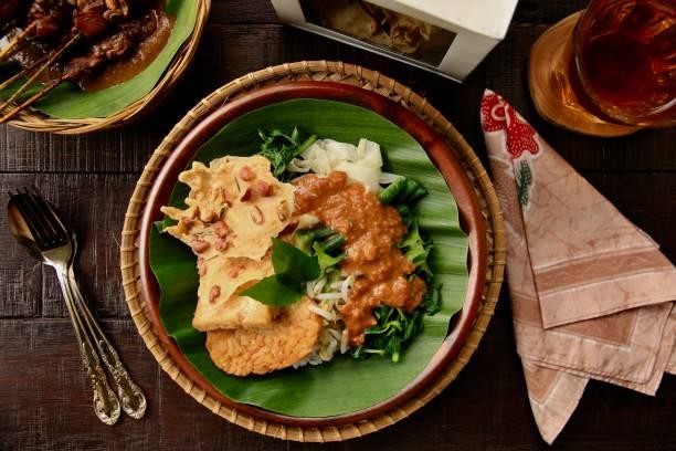 nasi pecel, einem traditionellen javanischen essen steames reis mit gemüsesalat - erdnusssalatdressings stock-fotos und bilder
