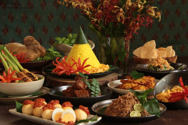 Nasi Tumpeng Nusantara, the Festive Indonesian Rijsttafel with Seven Side Dishes from Regional Cuisines Nasi Tumpeng Nusantara, the festive and grand Indonesian feast of rice mounted into cone shape and accompanied with seven other side dishes. In this particular feast, the side dishes are selected from several regional cuisines in Indonesia and plated individually. The side dishes are Javanese Braised Whole Chicken, Balinese Sate Lilit, Minangese Beef Rendang and also Eggs with Red Chili Paste, Minahasan Shredded Smoked Fish, Minahasan (and also Javanese) Corn Fritters, Javanese (and also Balinese) Vegetable Salad with Grated Coconut Dressing. A bowl of shrimp crackers and extra serving of the omelet strips are also served along. A bouquet of red and yellow orchids is placed on the table for decoration. A decorative Balinese woven textile is placed in the the background. manado stock pictures, royalty-free photos & images