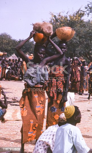 Natalgia. Northen Cameroon 1966.  Two women witha calabash bowls on their head at marketplace.. Two men with their back to the camera sitting in the foreground. Crowd of people in the background   +++ Scanned slides from 1966 +++