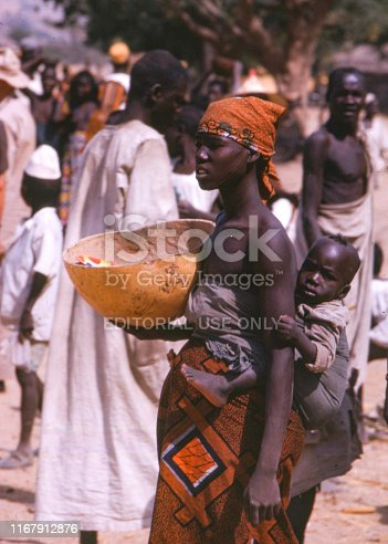 Natalgia. Northen Cameroon 1966.  Young woman with child on her back carrying a calabash bowl. In the background marketplace with crowd of people, men and woman.  +++ Scanned slides from 1966 +++