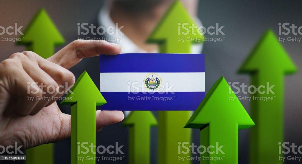 Concepto de crecimiento de nación, verde para arriba de las flechas - empresario sosteniendo la tarjeta de la bandera del Salvador - foto de stock