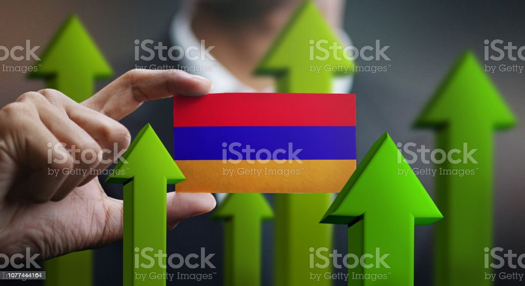 Nation Growth Concept, Green Up Arrows - Businessman Holding Card of Armenia Flag stock photo