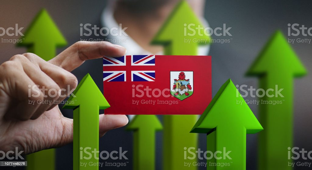 Nation Growth Concept, Green Up Arrows - Businessman Holding Card of Bermuda Flag stock photo