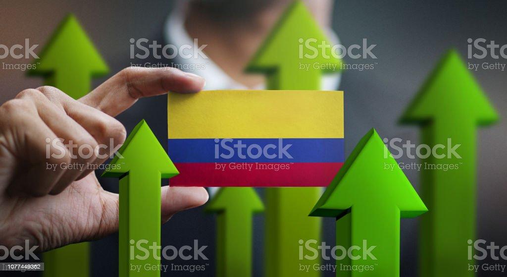 Concepto de crecimiento de nación, verde para arriba de las flechas - empresario sosteniendo la tarjeta de la bandera de Colombia - foto de stock