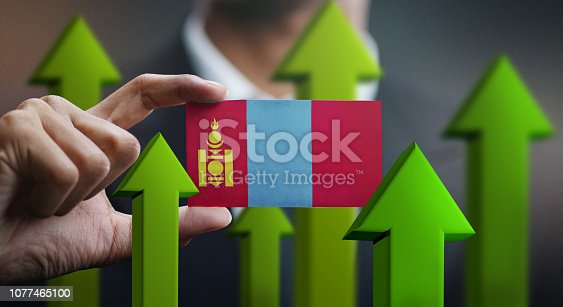 istock Nation Growth Concept, Green Up Arrows - Businessman Holding Card of Mongolia Flag 1077465100
