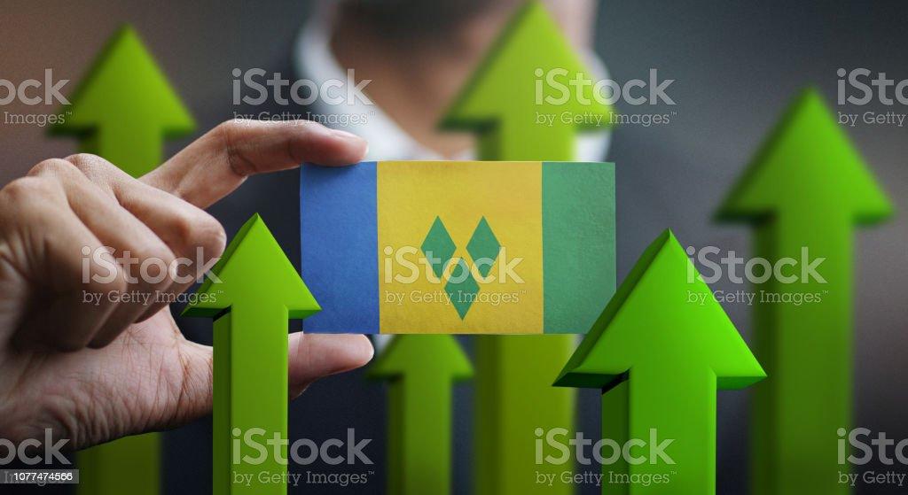 Conceito de crescimento de nação, verde em cima setas - empresário segurando o cartão da bandeira de São Vicente e Granadinas - foto de acervo