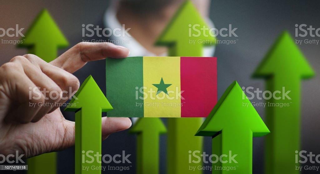Conceito de crescimento de nação, verde em cima setas - empresário segurando o cartão da bandeira do Senegal - foto de acervo