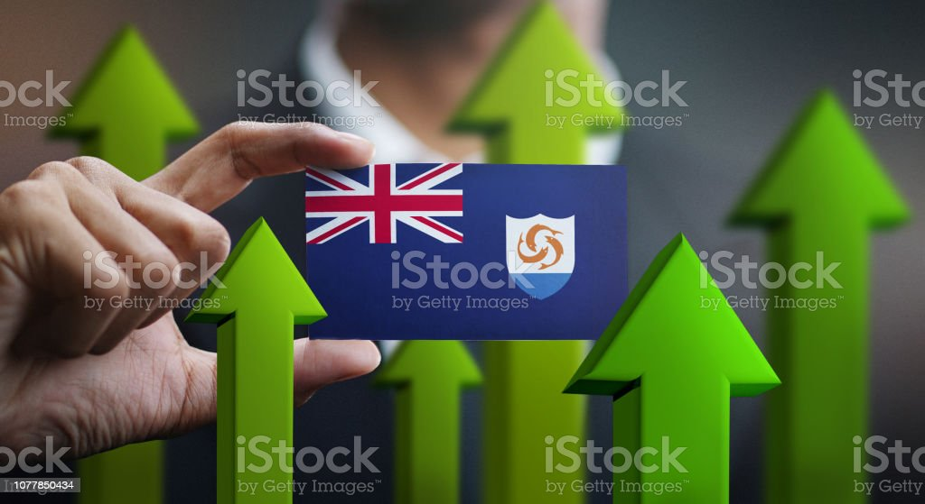 Nation Growth Concept, Green Up Arrows - Businessman Holding Card of Anguilla Flag stock photo