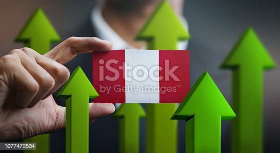 istock Nation Growth Concept, Green Up Arrows - Businessman Holding Card Peru Flag 1077472534