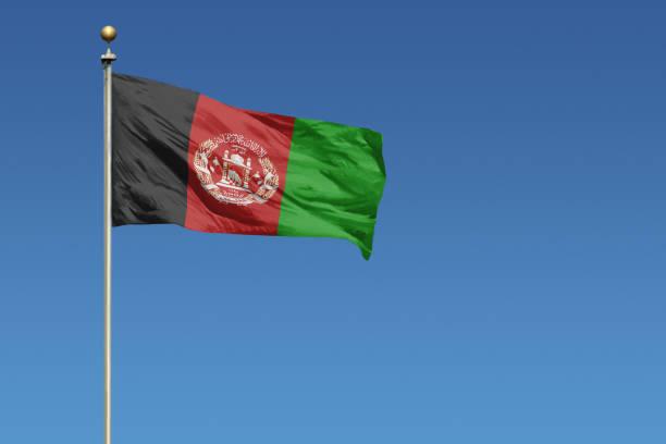 Bandeira nacional do Afeganistão na claro céu azul - foto de acervo