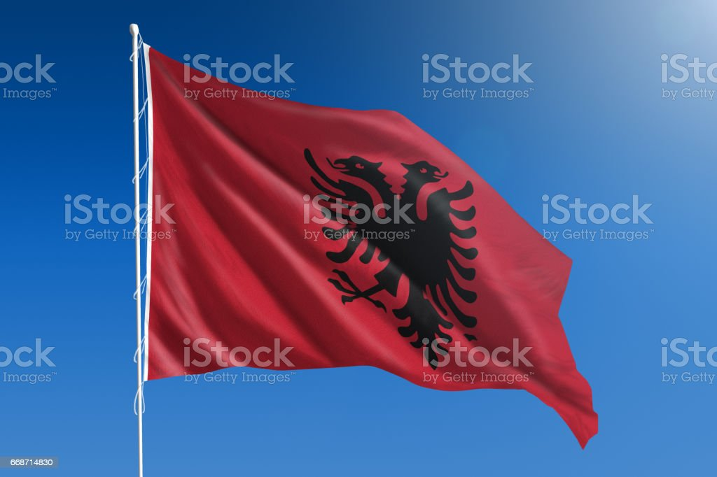 National flag of Albania on clear blue sky stock photo
