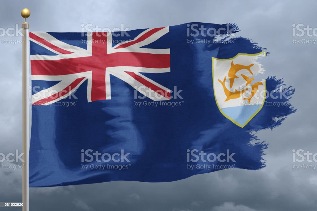 National flag of Anguilla with torn edge, in front of cloudy sky stock photo